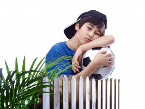 boy with a football leaning on the fence